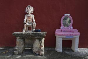 Dualidad entre juguete y mesa de piedra con muñeco prehispánico ubicada en el albergue Oasis para personas con VIH en Yucatán