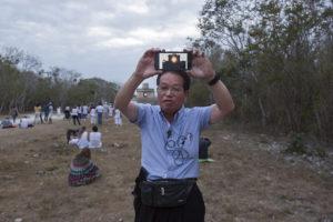 Guia de turistas japones enseña a su grupo de como se debió haber visto el fenónemo en Dzibilchaltún ante la salta de sol